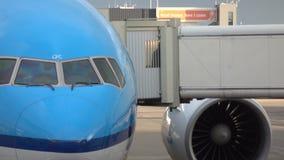 Passengers leaving a plane through jet bridge. People are seen through the jet bridge window. Shot in 4k stock video