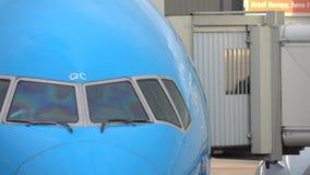 Passengers leaving a plane through jet bridge. People are seen through the jet bridge window. Shot in 4k stock video footage