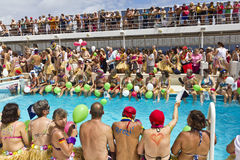 Passengers lined up on edge of pool. Mid Atlantic - Nov 11 2011: Passengers waiting on edge of pool for the Crossing the Equator Celebration on Cruise Ship MSC Royalty Free Stock Photography