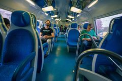 Passengers of a local train returning from work to the city, som. MILAN, ITALY - CIRCA NOVEMBER, 2015: Passengers of a local train returning from work to the Royalty Free Stock Photos