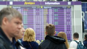 Passengers looking at timetable board screen at the airport, international flight. Boryspil, Ukraine - May, 2019: Passengers looking at timetable board screen at stock video