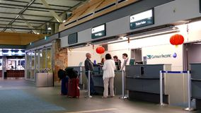 Passengers with luggage at Cathay Pacific check in counter stock footage