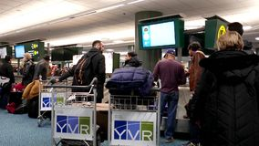 Passengers with luggage inside YVR airport. In Vancouver BC Canada stock footage