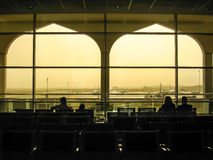 Passengers at Muscat airport in silhouette, Oman. Muscat, Oman - April 16, 2013: Couple passengers seated watching the aircrafts during waiting for boarding by Royalty Free Stock Photos