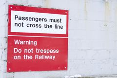 Passengers must not cross line at railway station safety notice sign stock photography