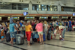 Passengers queue to check in at the airport Stock Photos