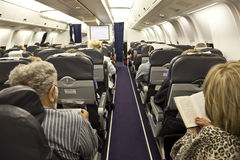 The passengers are reading in the cabin in flight. Stock Photos