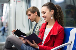 Passengers reading in metro wagon. Young passengers in metro wagon reading with electronic books stock photos