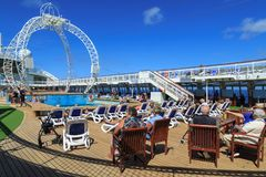 Passengers relax on the pool deck of a cruise liner royalty free stock photography