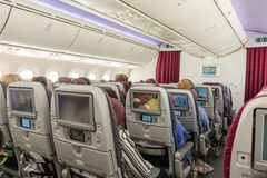 Passengers relax in the spacious cabin of Boing 787-8 Dreamliner. Passengers relax in a Boing 787-8 Dreamliner on a flight from Doha to Copenhagen, May 11, 2016 Royalty Free Stock Photos
