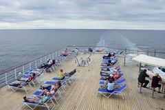 Passengers relaxing on deck of cruise ship out in open sea Stock Image