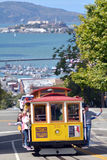 Passengers riding on Cable Car No. 15 with Alcatraz Island in th Stock Photo
