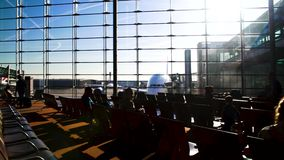 Passengers sitting on chairs in airport terminal, spacious sunlit waiting lounge. Stock footage stock video footage