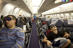 The passengers are sleeping in the cabin in flight