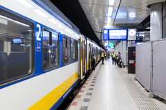 Passengers stand near the train at the Schiphol railway station. Royalty Free Stock Images