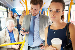 Passengers Standing On Busy Commuter Bus. Holding Takeaway Coffee And Mobile Phone royalty free stock photography