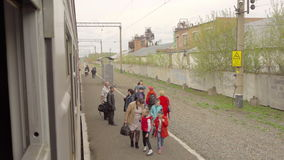 Passengers on Train stop. NOVOSIBIRSK REGION, RUSSIA - MAY 13, 2017: View from the window of the suburban train stock video footage