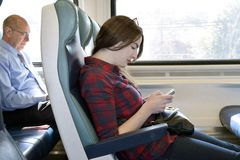 Passengers on a Train. Young Woman texts or plays video game on mobile phone traveling  on an off peak commuter train to New York City Royalty Free Stock Photo