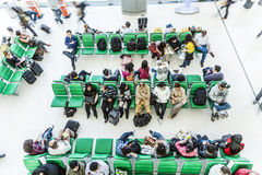 Passengers wait on benches for the departure of their flight Stock Image