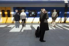 Passengers wait on pltform white train arrives at new railway st Royalty Free Stock Photo