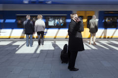 Passengers wait on pltform white train arrives at new railway st Royalty Free Stock Images