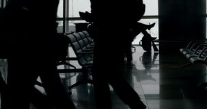 Passengers waiting in lounge of airport. Dolly shot of people walking and resting in the waiting-room of the airport. Rows of seats near big windows with airport stock video footage