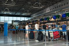 Passengers waiting in queue at American Airlines check in counter at Malpensa International Airport, Milan, Italy. Malpensa, Italy - August 13, 2015: passengers Stock Images
