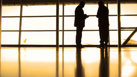 Passengers waiting to boarding in front of window in airport, silhouette, warm Royalty Free Stock Images