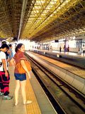 Passengers waiting at a train station Royalty Free Stock Images