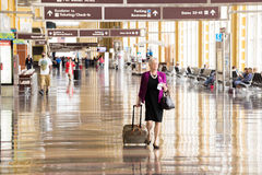 Passengers walking through a bright airport Stock Image