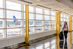 Passengers walking through a bright airport Stock Images