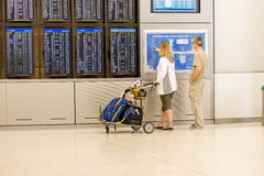 Passengers walking with lugagge in airport Stock Photos