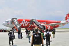 Passengers walking to Air Asia 330. The picture shows passengers walking towards an Airbus plane that belongs to Air Asia  at the Low Cost Carrier Terminal in Stock Photography