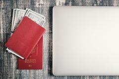 Passeport, argent et ordinateur portable sur la table en bois Photo stock