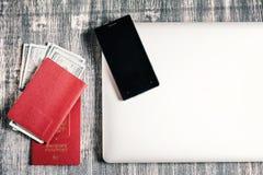 Passeport, argent, ordinateur portable sur la table en bois Photo stock
