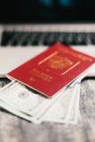 Passeport, argent, ordinateur portable sur la table en bois Image libre de droits