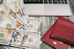 Passeport, argent, ordinateur portable sur la table en bois Photos stock