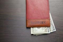 Passeport avec des billets de banque sur la table Vue supérieure Images stock
