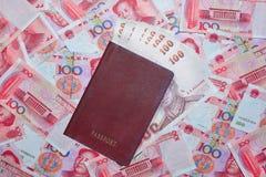 Passeport avec le baht thaïlandais sur le fond de devise de yuans Images libres de droits