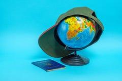 Passeport d'un citoyen de l'Ukraine pr?s du globe avec une casquette de baseball Noms g?ographiques sur le globe dans le Russe photos libres de droits