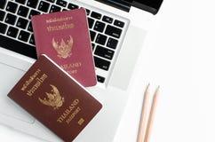 Passeport de la Thaïlande avec l'ordinateur portable sur le fond blanc, Image stock