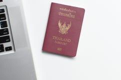 Passeport de la Thaïlande avec l'ordinateur portable sur le fond blanc, Photo libre de droits