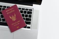 Passeport de la Thaïlande avec l'ordinateur portable sur le fond blanc, Photographie stock