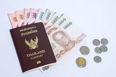 Passeport de la Thaïlande avec les billets de banque et les pièces de monnaie blancs de baht de fond Photo stock