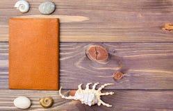 Passeport, pierre et coquillages sur un fond en bois Photo libre de droits
