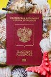 Passeport russe avec des coquillages de differernt sur le fond jaune photographie stock