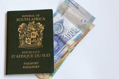 Passeport sud-africain avec des notes de devise Images stock