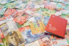 Passeport suisse et francs suisses avec de nouvelles 20 et 50 factures de franc suisse Photographie stock libre de droits