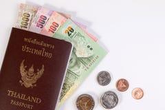 Passeport thaïlandais avec le billet de banque thaïlandais d'argent et la pièce de monnaie thaïlandaise d'isolement sur le blanc Photographie stock libre de droits