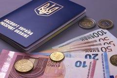 Passeport ukrainien international avec d'euro billets de banque d'isolement sur le fond gris Image stock